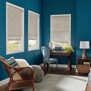 Klassisk inredning av ett stort huvudsovrum, med blå väggar, mörkt trägolv och brunt golv