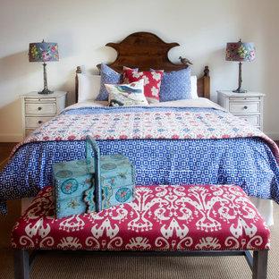 Diseño de dormitorio principal, clásico, grande, con suelo de madera oscura, paredes blancas, chimenea de doble cara, suelo marrón y marco de chimenea de piedra