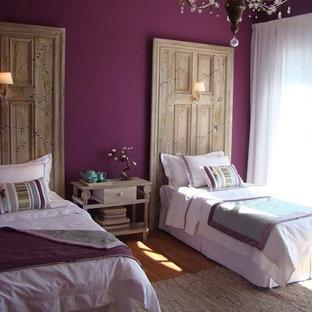 Modelo de habitación de invitados rural, de tamaño medio, con paredes rosas, suelo de madera oscura y suelo marrón