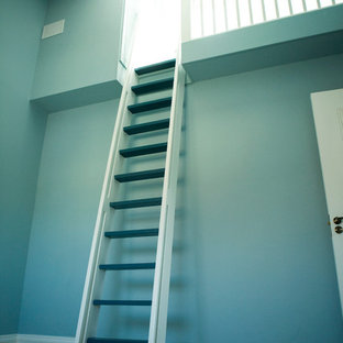 This is an example of a mid-sized traditional loft-style bedroom in Dublin with blue walls and carpet.