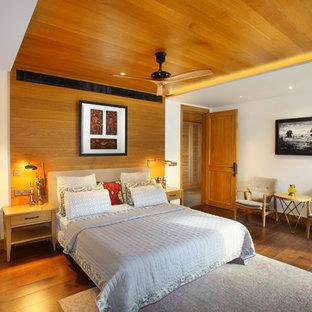Foto di una camera da letto design con pareti bianche, pavimento in legno massello medio e pavimento marrone