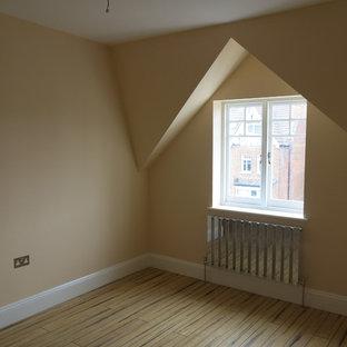 Foto de dormitorio tipo loft, contemporáneo, de tamaño medio, sin chimenea, con paredes beige, suelo marrón y suelo de bambú