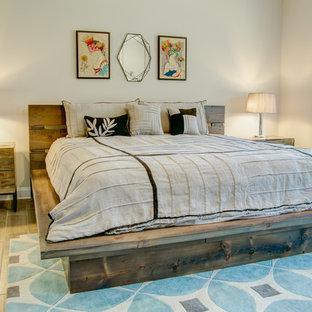 Design ideas for a large country master bedroom in Raleigh with brown floor, grey walls, light hardwood floors, a metal fireplace surround and no fireplace.