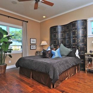 Example of an eclectic medium tone wood floor and orange floor bedroom design in Tampa with beige walls