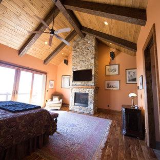 Inspiration för ett stort rustikt huvudsovrum, med orange väggar, mellanmörkt trägolv och en spiselkrans i sten