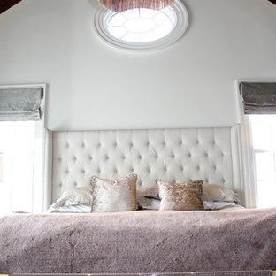 Modelo de dormitorio principal, actual, grande, con paredes blancas, suelo de madera oscura, chimenea lineal y marco de chimenea de ladrillo