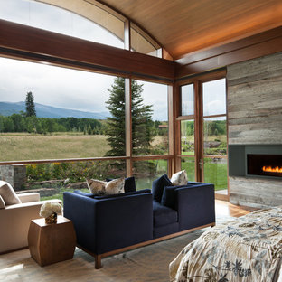 Design ideas for an expansive contemporary master bedroom in Denver with grey walls, dark hardwood floors, a ribbon fireplace, a metal fireplace surround and brown floor.