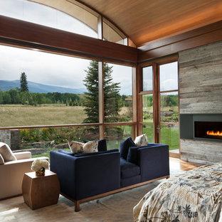 Diseño de dormitorio principal, actual, extra grande, con paredes grises, suelo de madera oscura, chimenea lineal, marco de chimenea de metal y suelo marrón