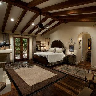 Modelo de dormitorio principal, mediterráneo, grande, con paredes beige, suelo de madera oscura, chimenea tradicional y marco de chimenea de yeso
