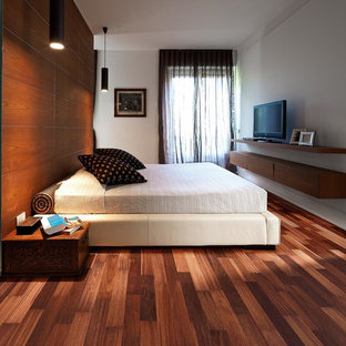 Mid-sized transitional loft-style bedroom in New York with brown walls, medium hardwood floors and red floor.