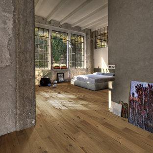 Mittelgroßes Industrial Schlafzimmer mit grauer Wandfarbe und hellem Holzboden in Chicago