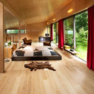 Foto de dormitorio principal, actual, de tamaño medio, con paredes marrones y suelo de madera clara