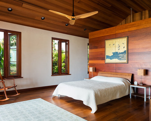 tropical bedroom idea in hawaii with white walls dark hardwood floors and brown floors