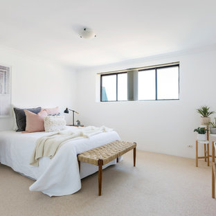This is an example of a beach style bedroom in Sydney with white walls, carpet and beige floor.