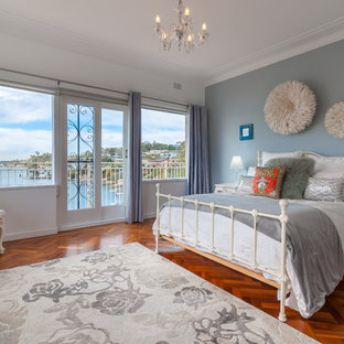 Photo of a traditional bedroom in Sydney with white walls, medium hardwood floors and brown floor.