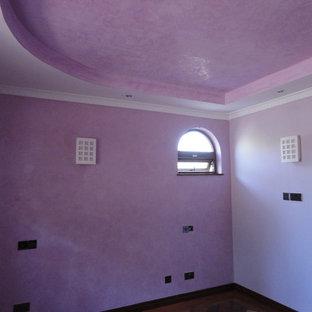 Imagen de dormitorio tipo loft, moderno, de tamaño medio, con paredes púrpuras y suelo de madera en tonos medios