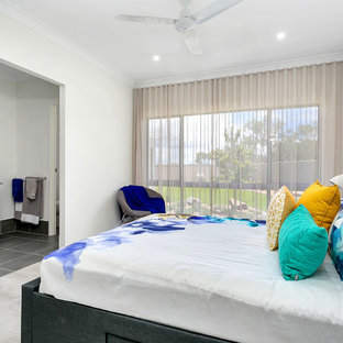 Contemporary master bedroom in Cairns with white walls and grey floor.