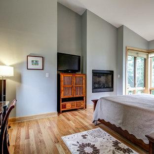 Foto de dormitorio principal, rural, de tamaño medio, con paredes grises, suelo de madera clara, chimenea tradicional y marco de chimenea de metal
