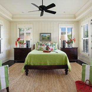 Immagine di una camera da letto tropicale con pareti bianche, parquet scuro e pavimento nero