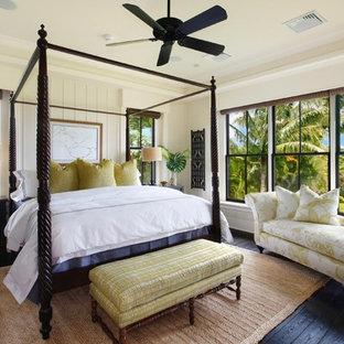 Foto de dormitorio tropical con paredes beige, suelo de madera oscura y suelo negro