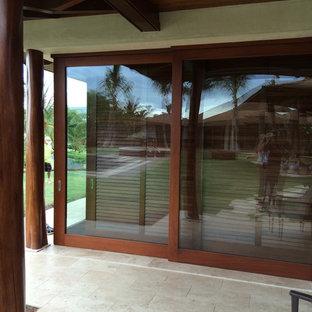 Foto di una grande camera matrimoniale tropicale con pareti beige, pavimento in travertino e nessun camino