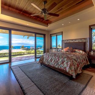 Diseño de dormitorio principal, exótico, grande, con paredes beige, suelo de madera clara y suelo multicolor