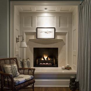 Imagen de dormitorio principal, clásico, grande, con paredes azules, suelo de madera en tonos medios, chimenea tradicional y marco de chimenea de piedra
