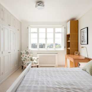 Medium sized classic bedroom in London with beige walls, carpet and beige floors.