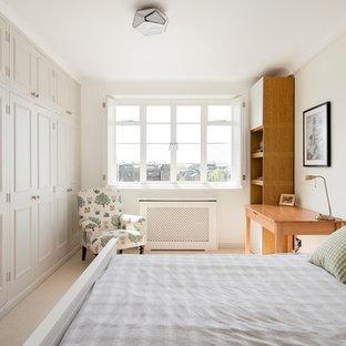 Modelo de dormitorio tradicional, de tamaño medio, con paredes beige, moqueta y suelo beige