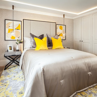 This is an example of a mid-sized transitional bedroom in London with medium hardwood floors and brown floor.