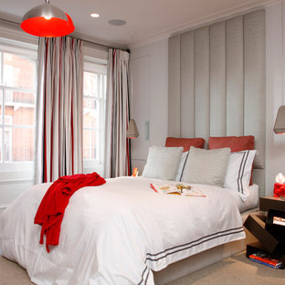 Example of a mid-sized trendy carpeted bedroom design in London with white walls