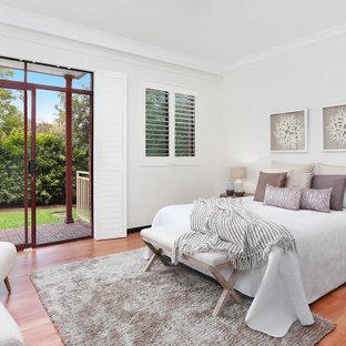 Modelo de dormitorio principal, tradicional renovado, de tamaño medio, con paredes blancas, suelo de madera clara y suelo naranja