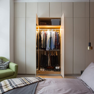 Contemporary bedroom in London with brown walls, carpet and beige floors.