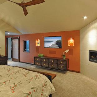 Foto di una camera matrimoniale minimal di medie dimensioni con pareti arancioni, moquette, camino lineare Ribbon e cornice del camino piastrellata