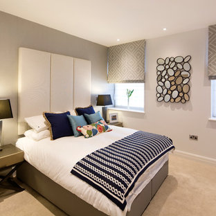 This is an example of a contemporary master bedroom in London with grey walls and carpet.