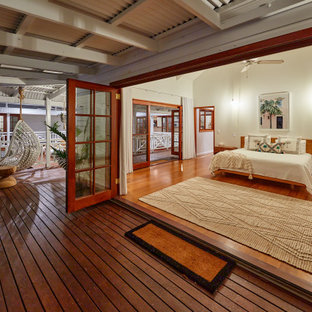 Inspiration for a tropical bedroom in Cairns with white walls, dark hardwood floors and brown floor.