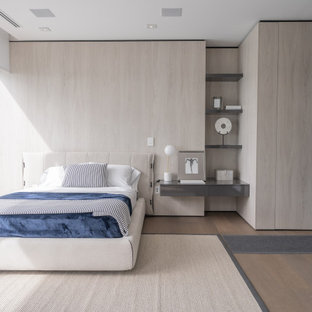 Modernes Schlafzimmer mit beiger Wandfarbe, braunem Holzboden, beigem Boden und Holzwänden in Miami