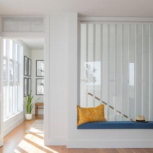 Idéer för ett stort maritimt huvudsovrum, med vita väggar, ljust trägolv och orange golv