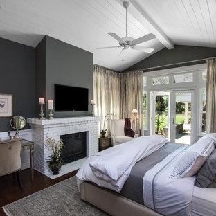 На фото: хозяйская спальня среднего размера в стиле современная классика с серыми стенами, темным паркетным полом, стандартным камином и фасадом камина из кирпича
