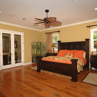 Example of a mid-sized island style master medium tone wood floor bedroom design in Tampa with beige walls and no fireplace