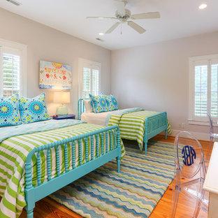 Foto di una camera degli ospiti stile marinaro con pareti beige e pavimento in legno massello medio