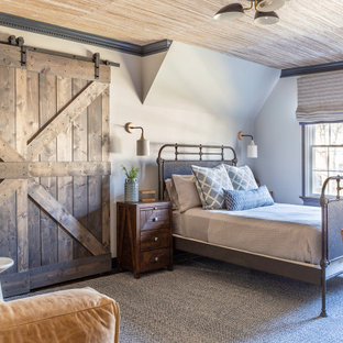 This is an example of a country bedroom in New York with white walls, carpet, grey floor and wallpaper.