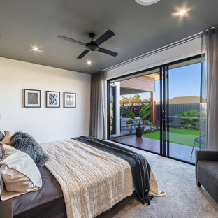This is an example of an expansive contemporary master bedroom in Brisbane with white walls, carpet and grey floor.