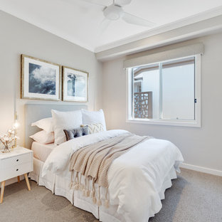 This is an example of a beach style guest bedroom in Brisbane with grey walls, carpet and beige floor.