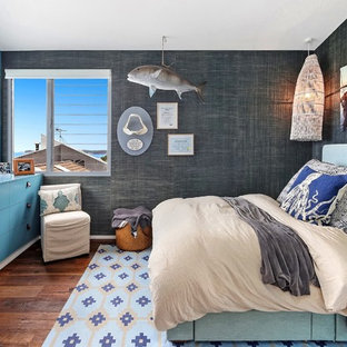This is an example of a tropical bedroom in Central Coast with grey walls, dark hardwood floors and brown floor.