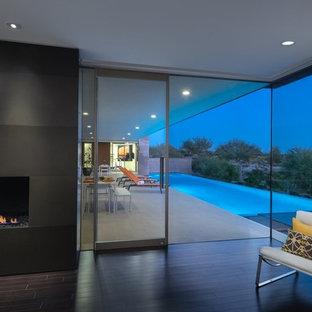 Стильный дизайн: хозяйская спальня среднего размера в стиле модернизм с белыми стенами, полом из бамбука, горизонтальным камином, фасадом камина из камня и черным полом - последний тренд