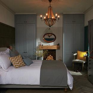 Idee per una camera matrimoniale design di medie dimensioni con pareti grigie, pavimento in legno verniciato, nessun camino e cornice del camino in pietra