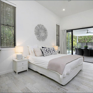 Large contemporary master bedroom in Central Coast with laminate floors, white walls and grey floor.