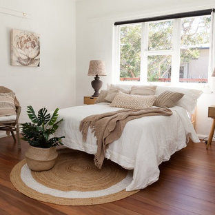 Inspiration for a beach style guest bedroom in Sunshine Coast with white walls, no fireplace, brown floor and medium hardwood floors.
