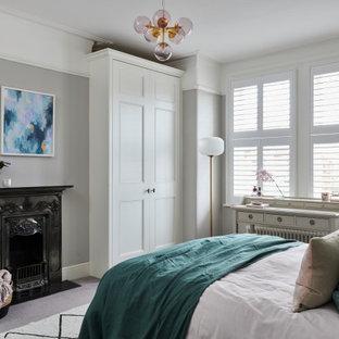 ケントの中くらいのトランジショナルスタイルのおしゃれな主寝室 (グレーの壁、カーペット敷き、標準型暖炉、金属の暖炉まわり、グレーの床) のインテリア